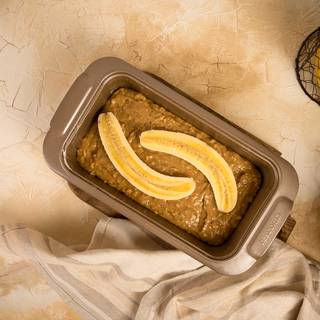 Pour the dough inside the tin. Cut a banana in half and drip some fresh lemon juice on it and place it on the dough. Put the tin inside the oven for about 50 minutes.