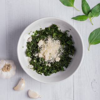 Put the basil leaves in a food processor or a mixer. After a few seconds add the parmesan cheese and mix them.