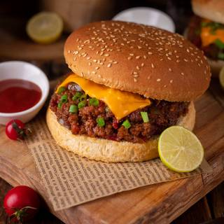 Sloppy Joe is usually served with burger buns. Put the beef inside a bun and cover it with cheese. You can also add lettuce, spring onions, pickled onions, some dill, hot sauce, chips, or anything you desire to your sandwich. Enjoy!