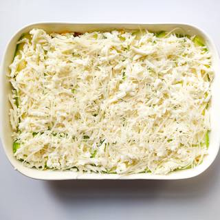 Pour the rest of the cheese on the zucchinis and spread it well.