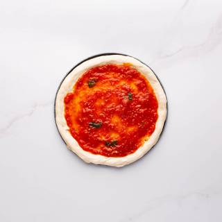 Spread Margherita sauce over the dough. Do not sauce the edges.