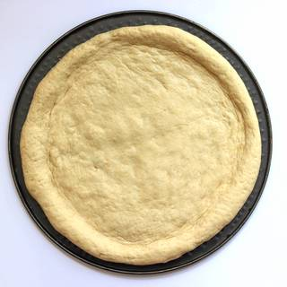 Ready-made pizza dough spread on a round pizza tray