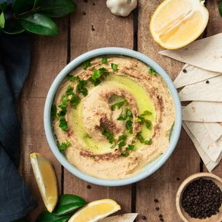 For decorating your hummus you can use olive oil, red pepper, and sliced parsley.
