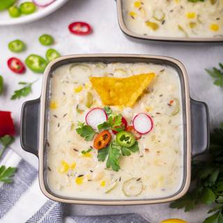 Serve your white bean chili in a proper dish. You can decorate it with parsley, radish, chili, and tortilla.