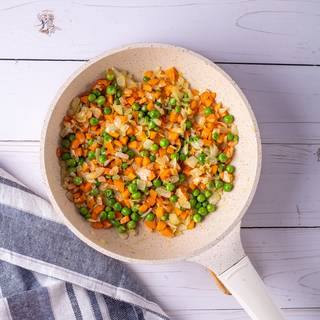 Fry the onions and garlic in a pan or a wok to make them soft. Add the carrots and peas and stir for 5 to 10 minutes until they are cooked. Then remove them from the pan.