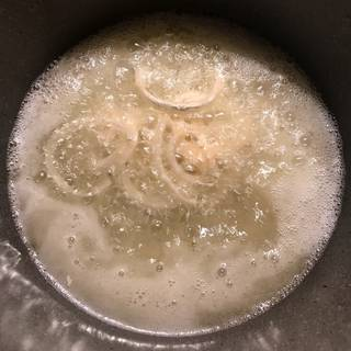 Pour enough oil in a pot over medium heat and then plunge a handful of onions into the oil when it's hot enough and fry them.
