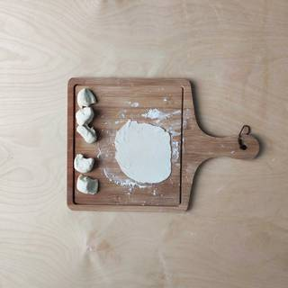 Sprinkle some flour on a surface. Press the doughs into round disks with your hands. Use a rolling pin to make them a little thinner. Don't make them too thin.