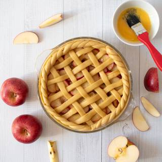 Roll out the rest of the dough and cut it in stripes, put it on the pie, and stick it to the pie crust. cut the extra remaining dough carefully. Beat the yolk and brush the dough, then place the dough on top of the pie in a lattice formation.