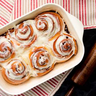 Finally, after the rolls are cool enough, spread the icing evenly over the cinnamon rolls.