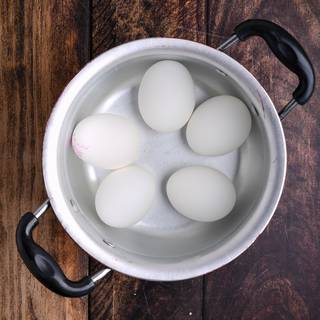 Wash the eggs and put them in water on medium heat until the water comes to a boil.
