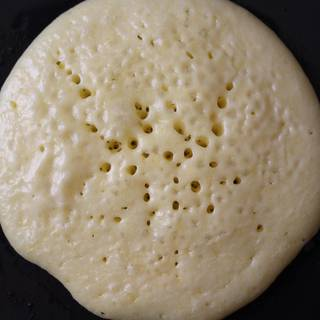 Cook until the surface of pancakes has some bubbles and a few have burst. Flip it over and cook until browned on the underside,