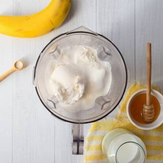 In this step, add 3 scoops of ice cream, and vanilla to milk and banana then mix them completely. Now we can add sugar or honey to them as desired.