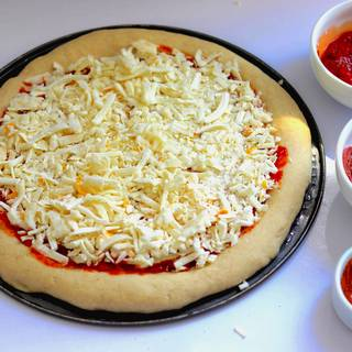 Spread the mozzarella on the surface of the dough, except on the margin, so that it completely covers the dough.