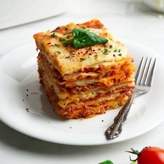 Photograph of lasagna garnished in a white dish