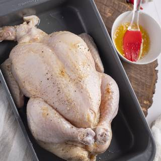 After trussing your chicken, use a brush to grease it with butter.