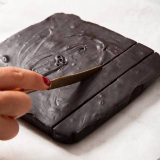 Put the fudge on an even surface and remove the parchment paper.