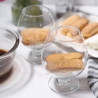 Rolling ladyfingers in coffee and put them on plate, but please pay attention. Don't let ladyfingers be submerged for a long time in the coffee because they will become soggy and as a result, the whole tiramisu becomes wet.