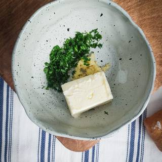 Take the butter out of the fridge to become room temperature. chop the parsley. peel the garlic and crush them.