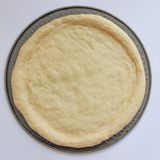 Spread the pizza dough on a round tray ready to put in the oven