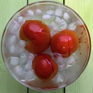 Remove the tomatoes from boiling water and plunge them into the iced water to cool them down quickly.