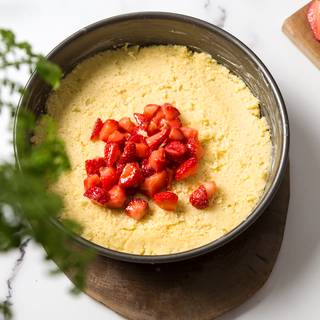 Use 2/3 of the dough to cover the bottom of the pan and make it smooth and even by pressing it with a spoon or your hands. Place the strawberries on top of the dough.