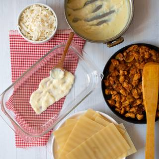 Now, grease into the baking dish and spread a layer of Béchamel sauce.