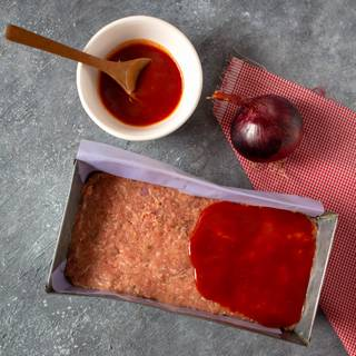 Place in a greased rectangular baking dish and form into a loaf or place in a greased loaf pan. Pour ketchup sauce over it and cover with aluminum foil. Bake at 350 degrees F for 45 minutes. Then remove the foil and place it in the oven for 30 minutes again.