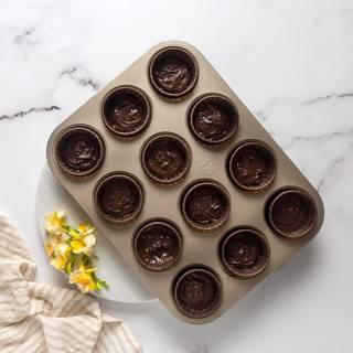 Put the cupcake capsules inside the cupcake tin and fill 2/3 of the capsules with your dough.