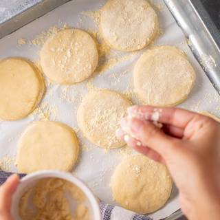 Cover a tray with parchment papers and sprinkle some corn flour on them. Place the muffins on the tray and sprinkle corn flour on them. cover the tray and let it rest for one more hour to become larger.