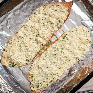 Grate the parmesan cheese and sprinkle it on the bread. Put the bread inside the oven for about 10 to 15 minutes at 170C.