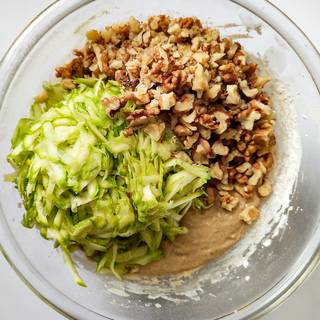 Grate the zucchini and chop the walnuts, then mix it with the batter.