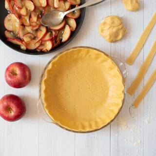 Roll out the dough with a rolling pin and make it about 3 inches bigger than your baking pan. Put the dough inside the pan and cut the extra with a knife. fill the pie crust with the apples.