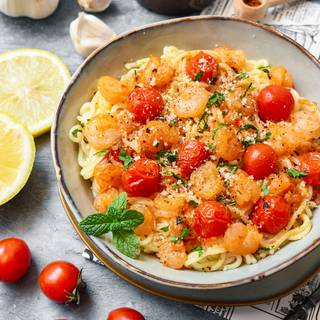 Our spaghetti with shrimps and tomatoes is ready now. You can decorate it with some fresh chopped parsley and parmesan cheese.