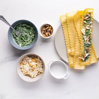 Place the lasagna on a flat plate and put spinach, mushrooms, and mozzarella cheese on top, then roll the lasagna.