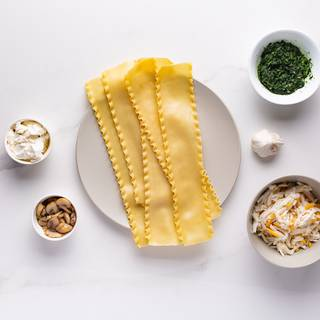Cook the spinach with one clove of garlic and some oil. Cook the mushroom with oil, salt, and pepper. Boil the lasagna too.