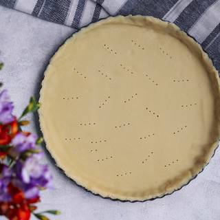 After one hour, roll out the dough with a rolling pin, then transfer it to a pie pan. Create small holes in the bottom with a fork to prevent your crust to rise.