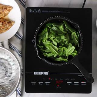Adding spinach to a cast-iron frying pan