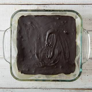 Take the fudge out of the fridge. you can take the fudge out easily with a little help from the parchment paper that you have greased before.