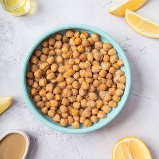 The main ingredient for the hummus is chickpeas. You can cook them yourself or buy them canned. If you want to cook them yourself, soak them in water overnight and change the water a couple of times. You can cook the chickpeas the next day in the water on low heat until they become soft.