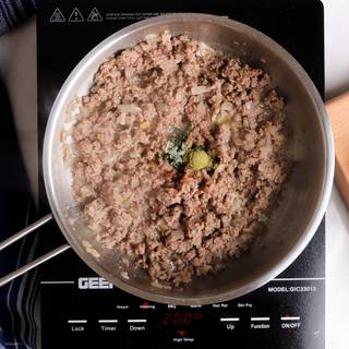 Sautéing meat and spices in a steel pan