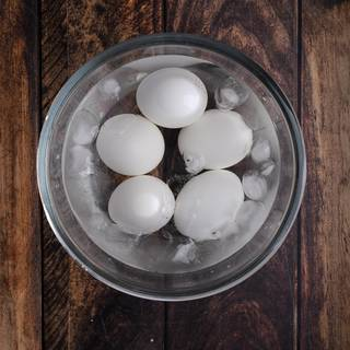 Take the eggs out of the boiling water after 20 minutes and put them in ice water. This helps you remove the shell easier.