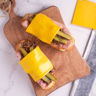 Put pickles and the gouda cheese on top of each other and finally place the other side of the baguette on top of your sandwich.