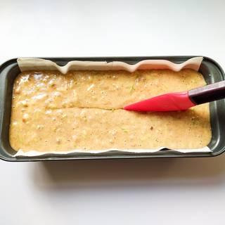 Put parchment paper at the bottom of the loaf pan and pour the batter into the loaf pan. Dip an oil-covered spatula and make a slit in the middle of the cake if you want to have a crack in the middle.