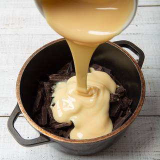 Add the chocolates into a pot and then add the condensed milk to it.