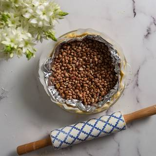 Put some foil on the parchment paper and fill it with beans. Preheat the oven at 200C and bake your crust for 15 to 20 minutes, then take it out and remove the foil and the parchment paper.