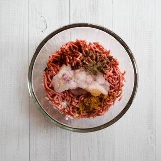 Season your beef with spices. Add the grated onion and minced garlic to your beef. There is no need to remove the excess water because it helps your beef to be cooked better. Knead the beef well for 5 minutes.