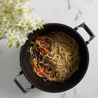 Now add the chicken and the noodles to the vegetables and mix them well. Add the rest of the sauce to your pan and fry them on high heat.